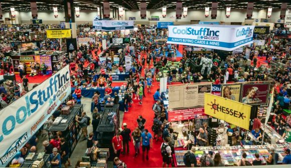 A busy room from Gen Con 2021 full of stalls and people wandering between aisles
