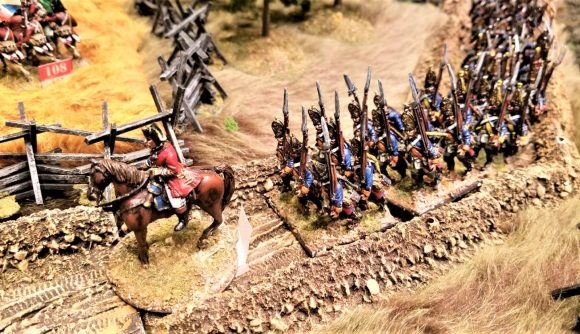 Photo of napoleonic soldier miniatures on a tabletop road at a Historicon convention