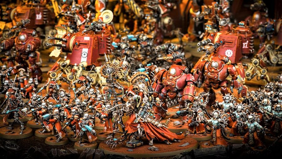 Warhammer Community photo showing a large Adeptus Mechanicus army for Warhammer 40k, in Mars colours, with Onager Dunecrawlers, Skitarii and Electropriests