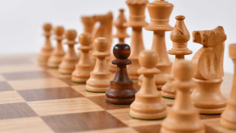 How to play chess pieces lined up in a row, credited to Randy Fath on Unsplash