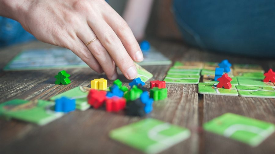Best couples' board games - photo showing a player's hand moving tiles and pieces in a game of Carcassonne