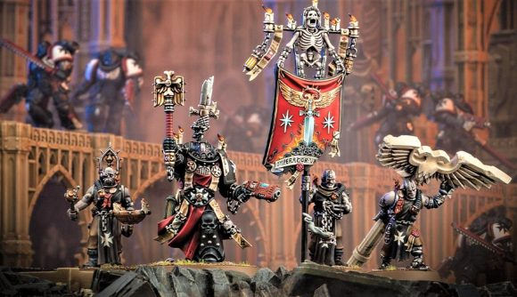 Warhammer 40k Black Templars Primaris Chaplain Grimaldus revealed - Warhammer Community photo showing the new model for a Primaris Chaplain Grimaldus, with his attendant servitors, with an Imperial structure in the background